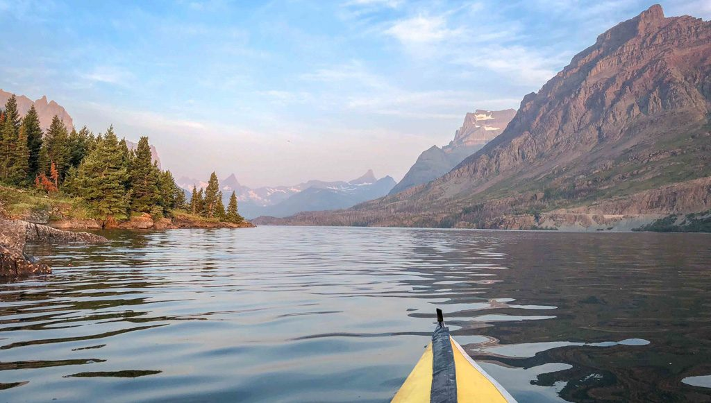 Tip of a yellow kayak on the water, with pine trees, mountains, and hazy blue sky in the background.