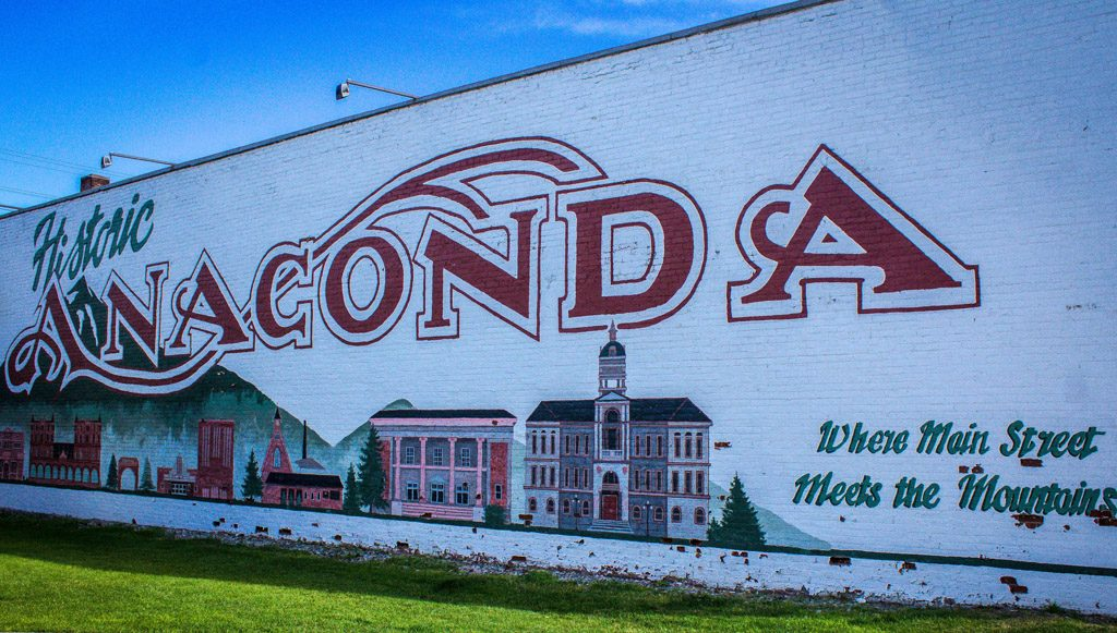 "An outdoor mural of buildings and the text ""Historic Anaconda. Where Main Street Meets the Mountains."""