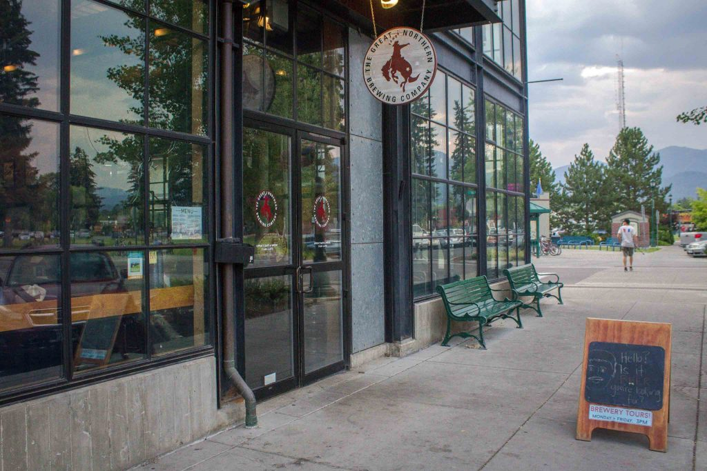 """Exterior of a glass building with circular signs reading """"Great Northern Brewing Company,"""" with a sidewalk, trees, and hazy mountains in the background."""