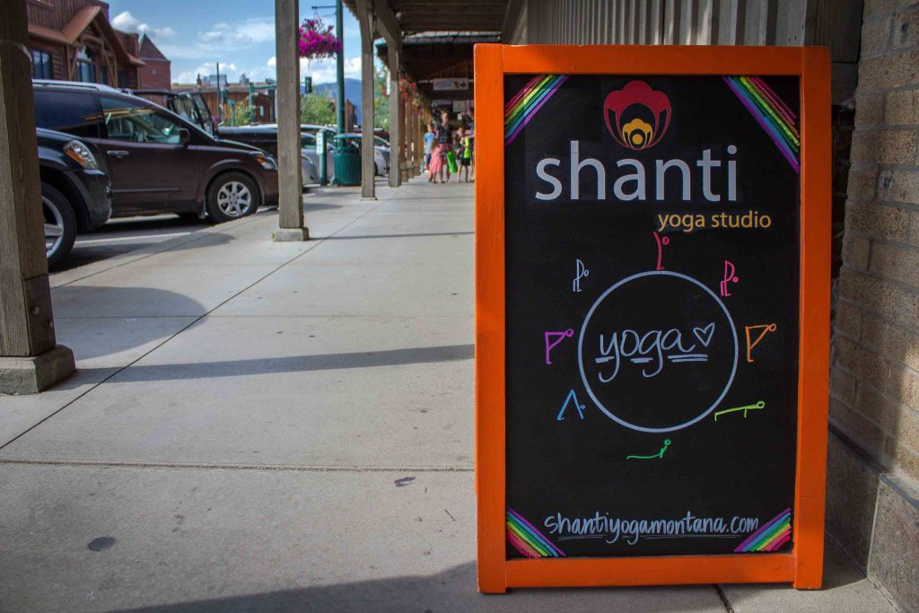 "Red-framed chalkboard sign reading ""shanti yoga studio,"" above stick figures of yoga poses in a circle around the word ""yoga,"" sitting on a sidewalk with pedestrians and parked cars in the background."