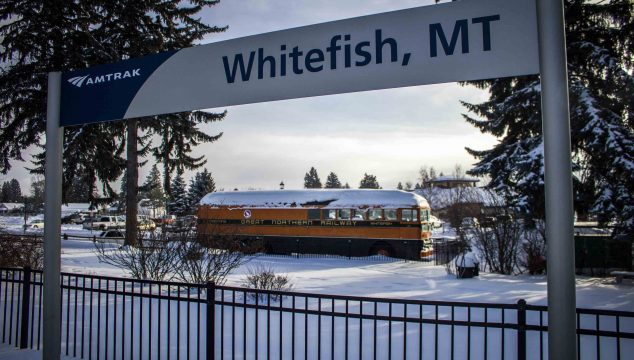"""Whitefish, MT"" Amtrak sign in front of a metal fence, with a snow-covered yellow train car reading ""Great Northern Railway"" in the background."