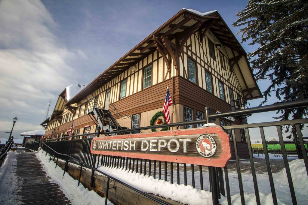 "Sign reading ""Whitefish Depot"" with the Great Northern Railway logo on a metal fence, in front of a yellow and brown three-story building, with snow on the ground."