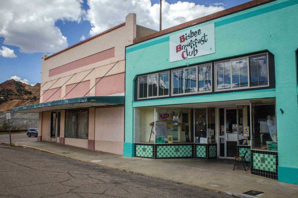 "A plain salmon-colored building next to a turquoise building with a sign reading ""Bisbee Breakfast Club."""