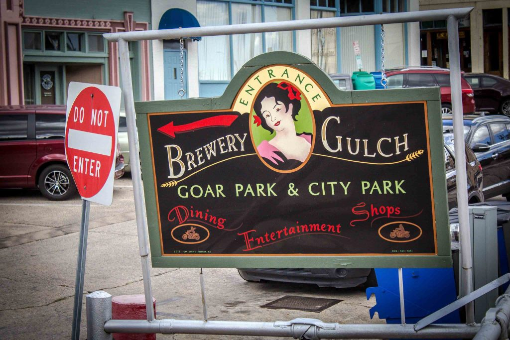 "Outdoor sign with a painting of a woman, a red arrow, and the words ""Entrance. Brewery Gulch. Goar Park & City Park. Dining Entertainment Shops,"" next to a Do Not Enter sign."