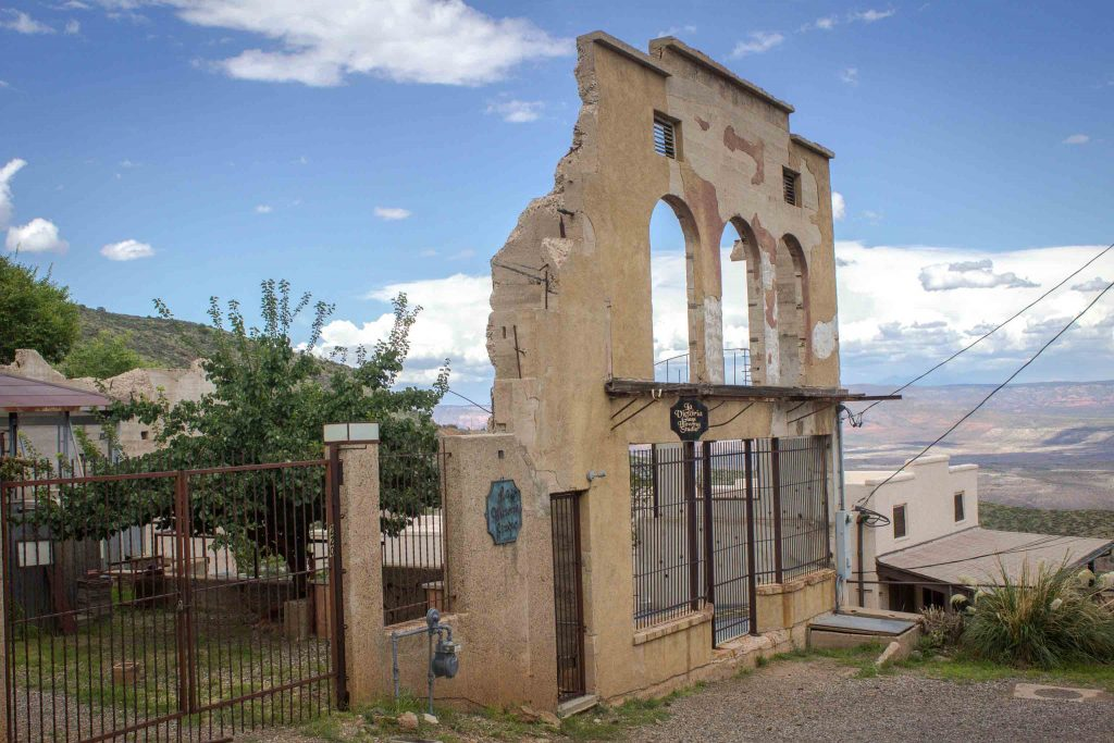 Facade of a crumbling tan building, with a bare landscape in the background.