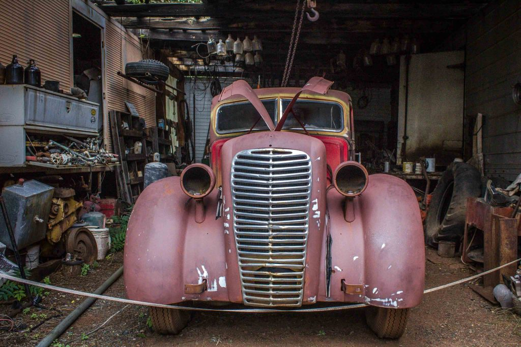 Antique red car sitting inside a garage.