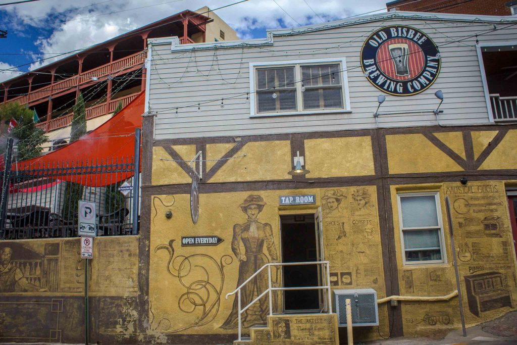 "Outside of a yellow building covered in faded drawings, below a round red and blue sign reading ""Old Bisbee Brewing Company."""