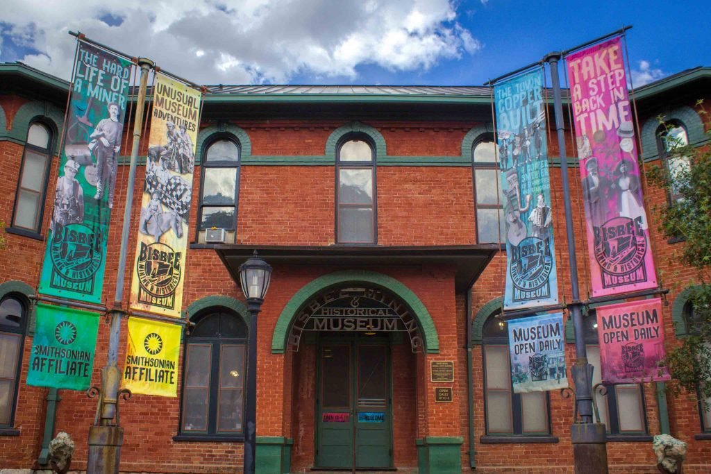 "Brick building with green trim and an arched doorway with a sign reading ""Bisbee Mining and Historical Museum,"" and four colorful banners in front."