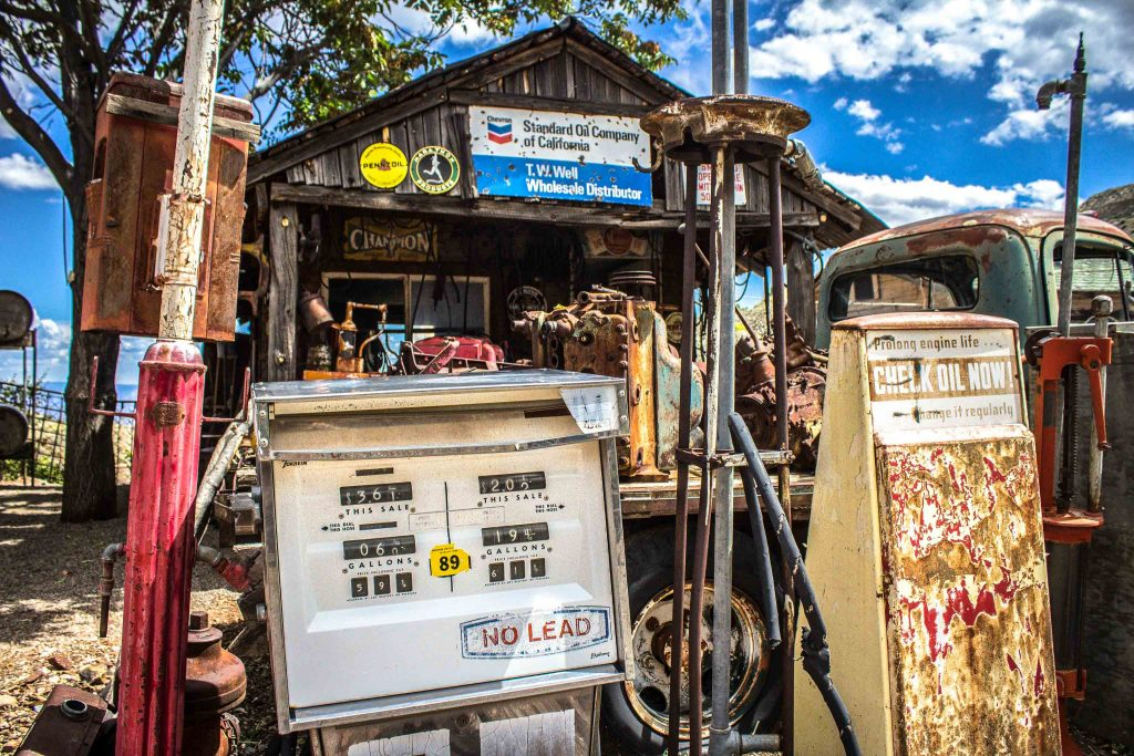 """Abandoned gas pumps in front of a wooden building with a sign reading """"Standard Oil Company of California. T.W. Well Wholesale Distributor."""""""