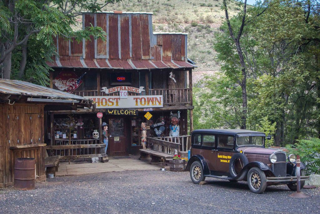 "Brown old-timey car in front of a two-story wooden and metal building, with a sign above the entryway reading, ""Entrance to Ghost Town. Welcome."""