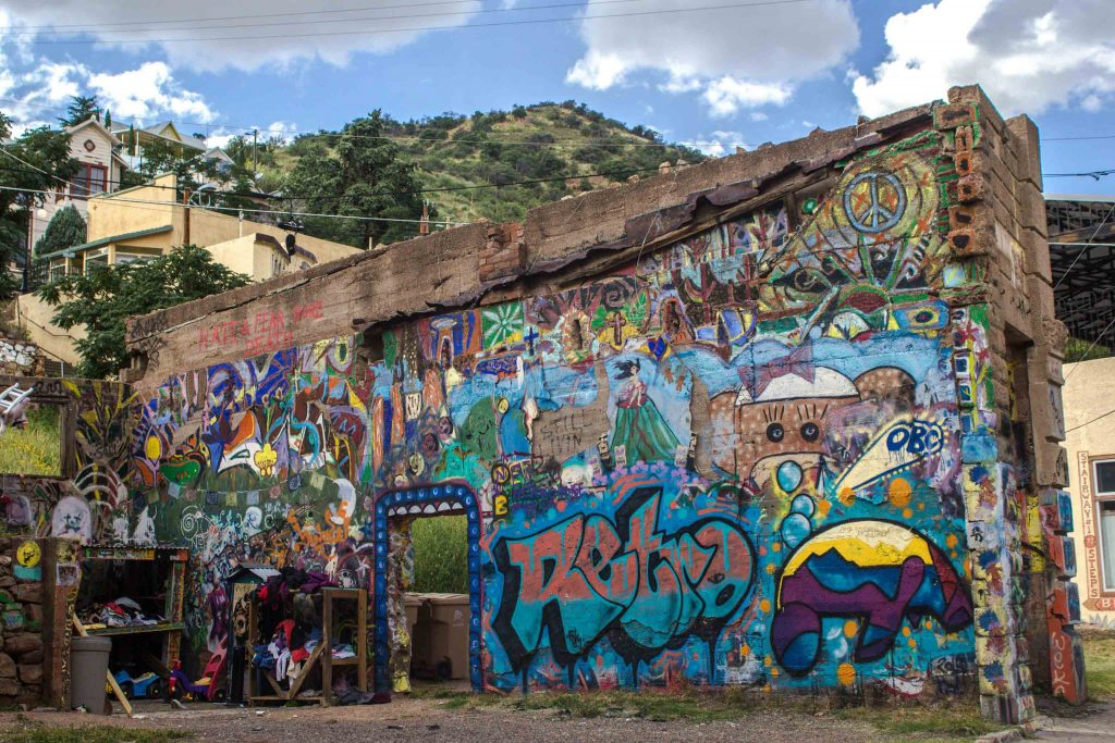 A crumbling brick wall covered in bright graffiti, in front of a tall grassy hill.