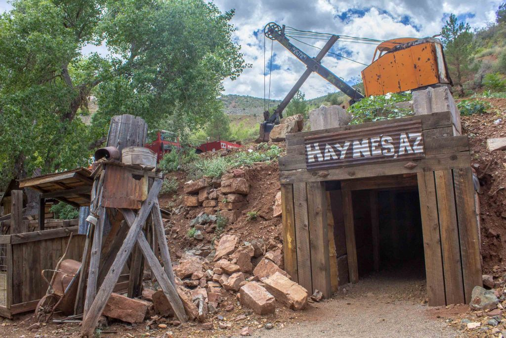 """Rusted equipment by a wooden entrance in the side of a dirt hill, under a sign reading """"Haynes, AZ."""""""