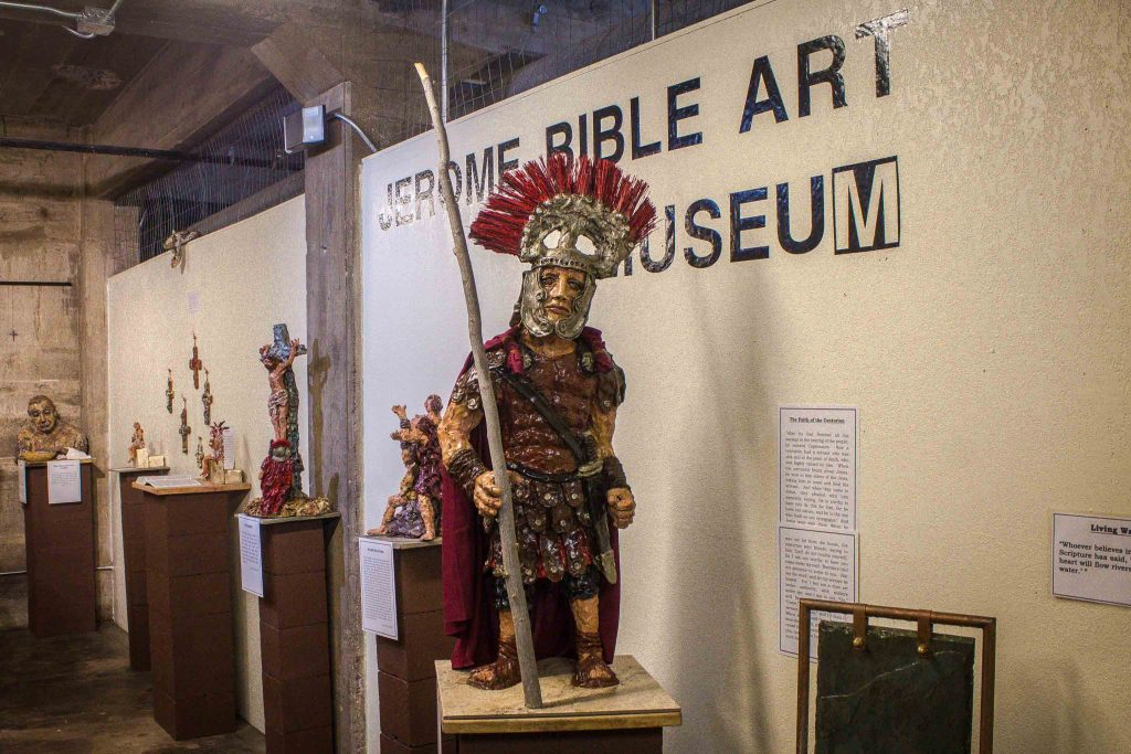 """Gladiator figurines on pedestals in front of a wall reading """"Jerome Bible Art Museum."""""""
