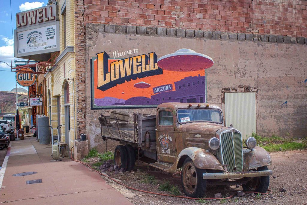 "A run-down old truck sitting in front of a brick wall with a bright mural of UFOs and buildings, reading ""Welcome to Lowell Arizona."""