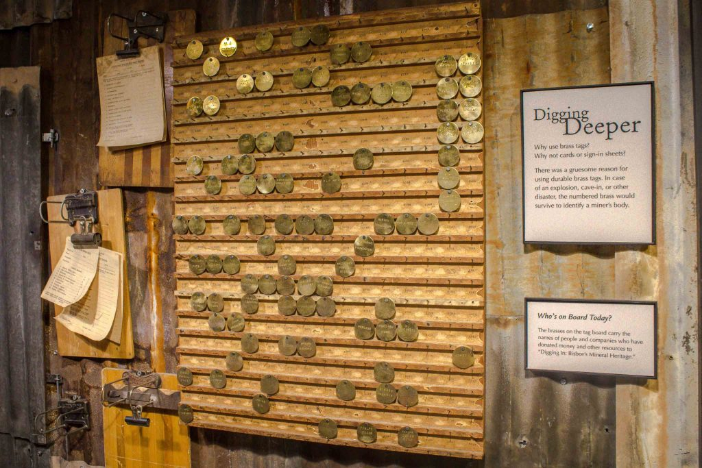 "Museum display of a hanging board lined with brown coins, next to a placard titled ""Digging Deeper."""