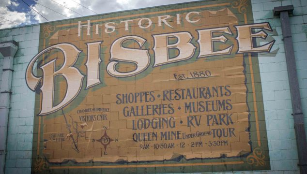 "White brick exterior wall with tan mural reading ""Historic Bisbee Est. 1880. Shoppes, Restaurants, Galleries, Museums, Lodging, RV Park, Queen Mine Underground Tour."""