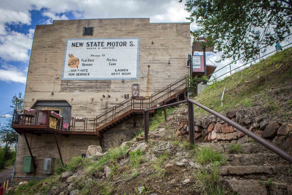 "Side of a building with an exterior staircase and a sign reading ""New State Motor Co."""
