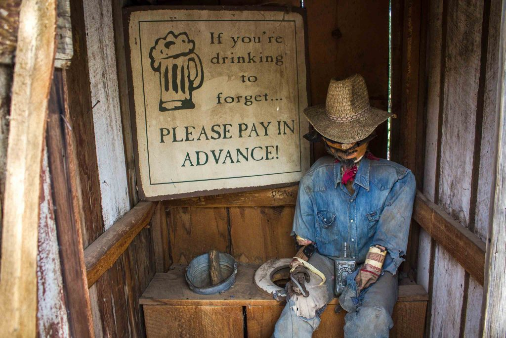 """Interior of an outhouse with a mannequin dressed like a cowboy sitting next to the toilet seat, and a sign on the wall reading """"If you're drinking to forget…Please pay in advance!"""""""