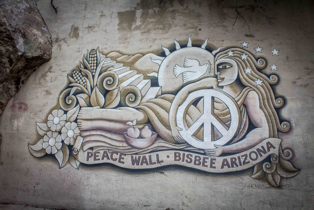"A mural of a reclining woman holding a white peace sign, above the words ""Peace Wall Bisbee Arizona,"" with a staircase, sun, and dove in the background."