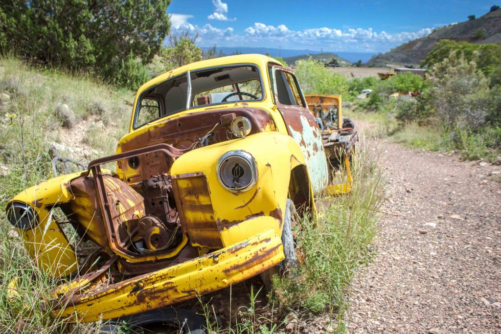 Old rusted yellow car sitting in the brush next to a dirt path, with a blue sky in the background.