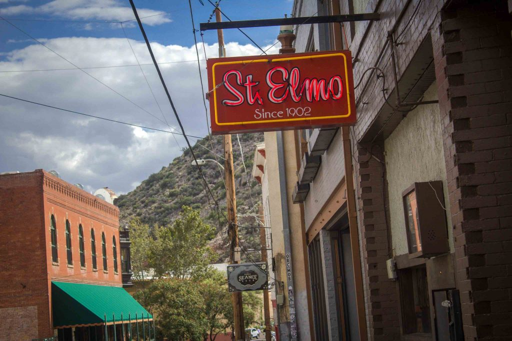 "Red light-up sign reading ""St. Elmo Since 1902,"" mounted on the outside of a building, with a grassy hill in the background."