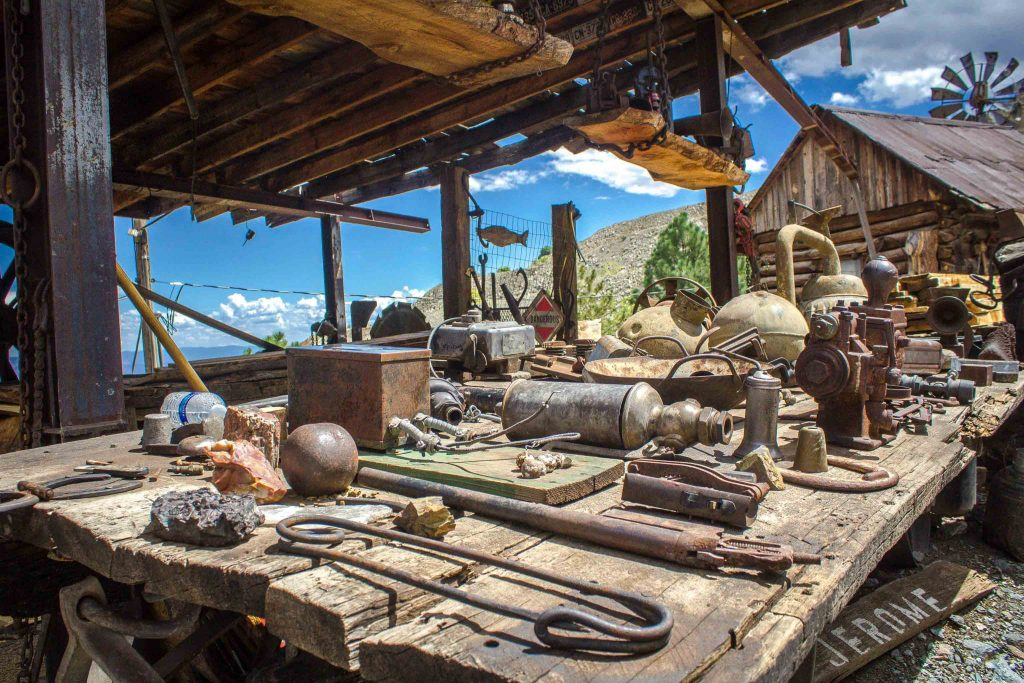 A wooden platform covered in old tools and equipment, in front of a log building and windmill.