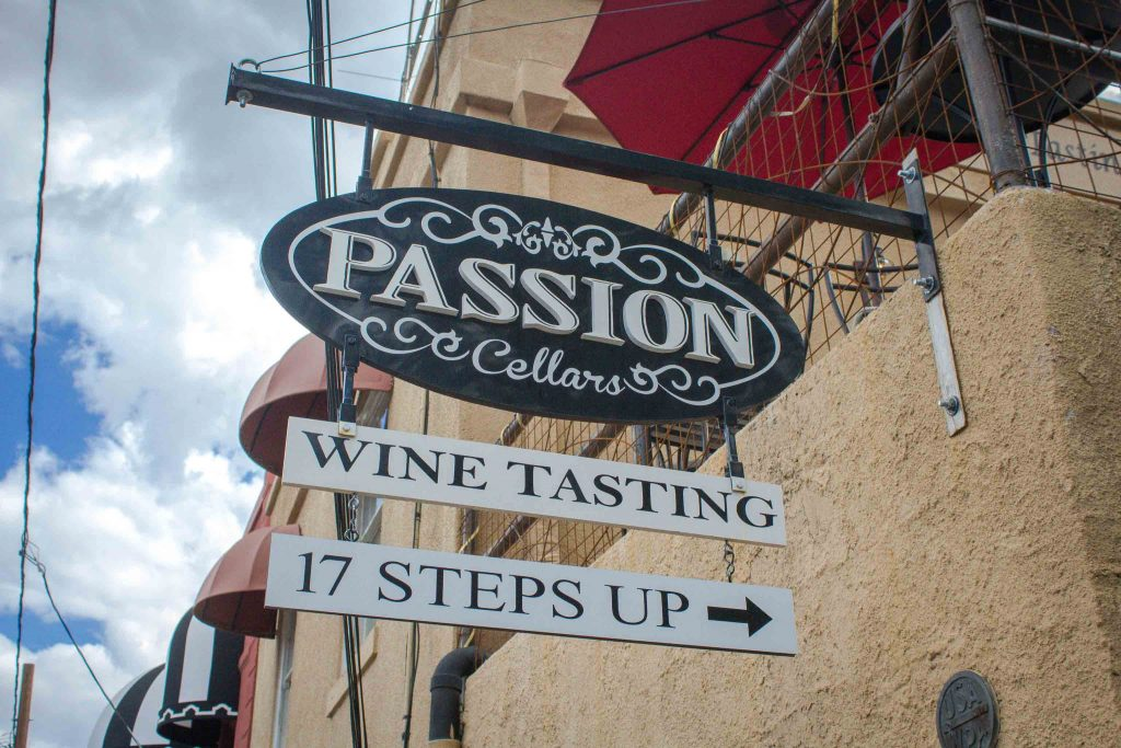 """Sign mounted on a the side of an adobe building reading """"Passion Cellars. Wine tasting. 17 steps up."""""""