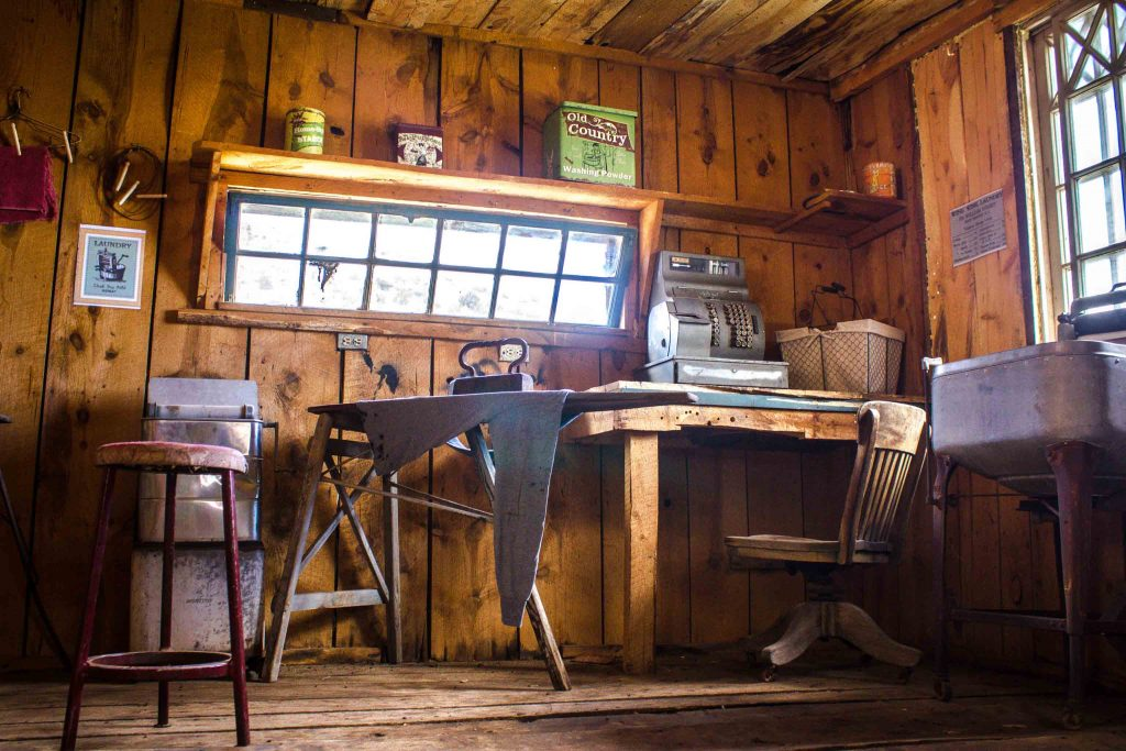 Interior of a wooden building with a desk and an antique ironing board and cash register.