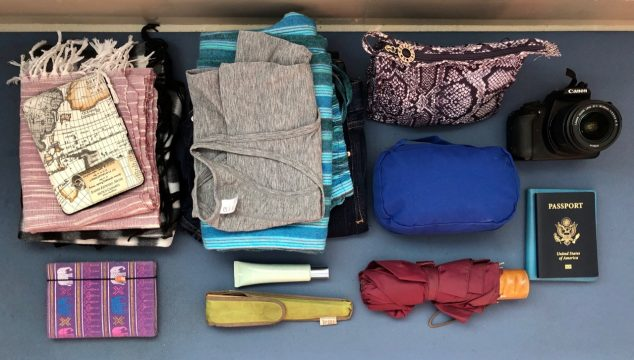 Rows of small bags, piles of folded clothes, and items like a notebook, camera, umbrella, and U.S. passport, on a blue background.