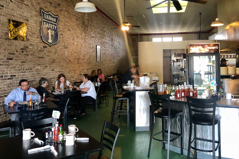 People eating at tables inside a casual restaurant, with a green floor and exposed brick wall.
