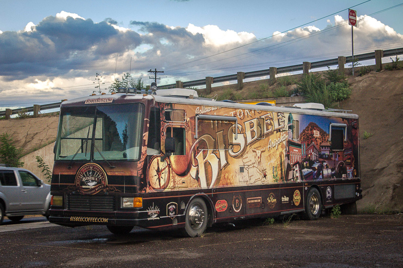 "Bus in a parking lot painted with a tan mural reading ""Historic Bisbee Arizona."""