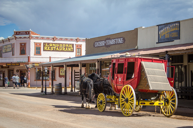 Two black horses pulling a red stagecoach down a road, past Wild West-style buildings.