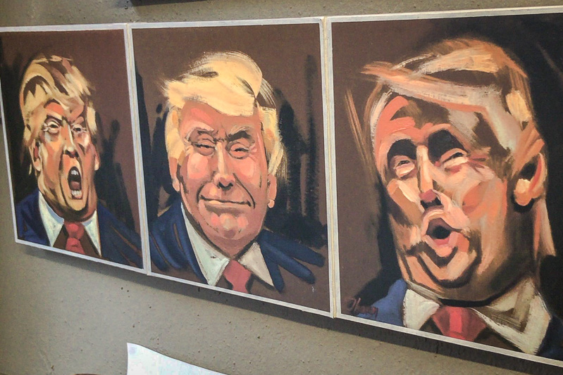 Horizontal painting with three frames, with a cartoonish portrait of Donald Trump making a different stereotypical facial expression in each one.