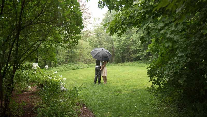 Jen and Ryan standing under an umbrella in a field, at our wedding in Vermont.