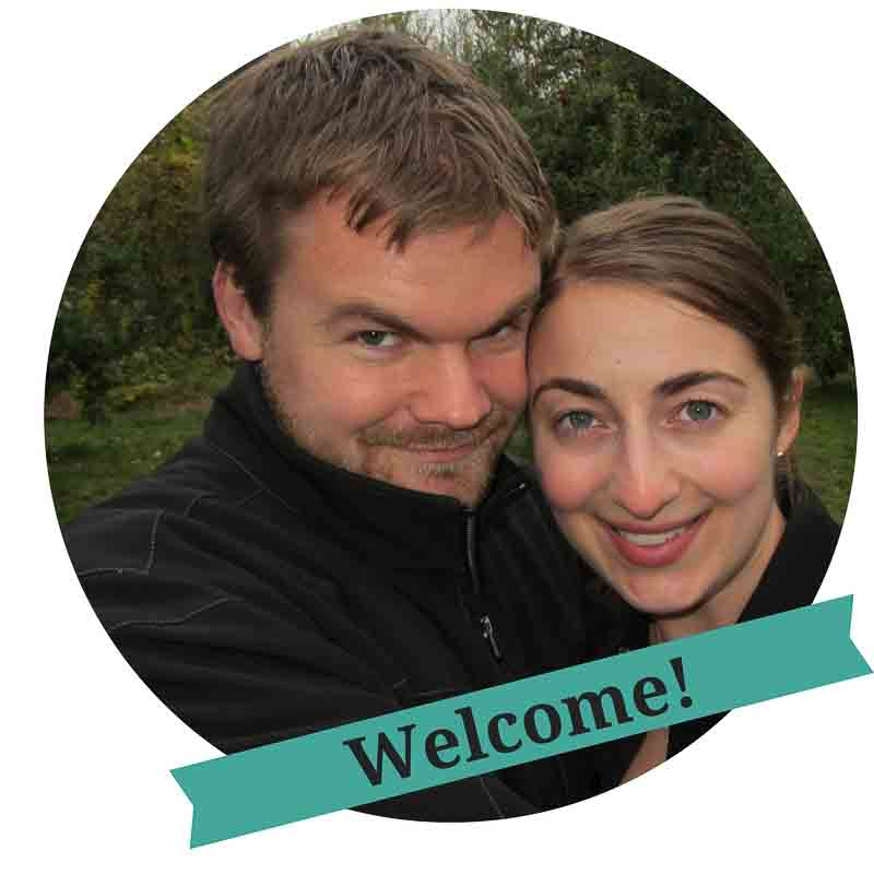 "Close-up of a white man and woman both wearing black with trees in the background, and an overlaying green banner that says ""Welcome!"""