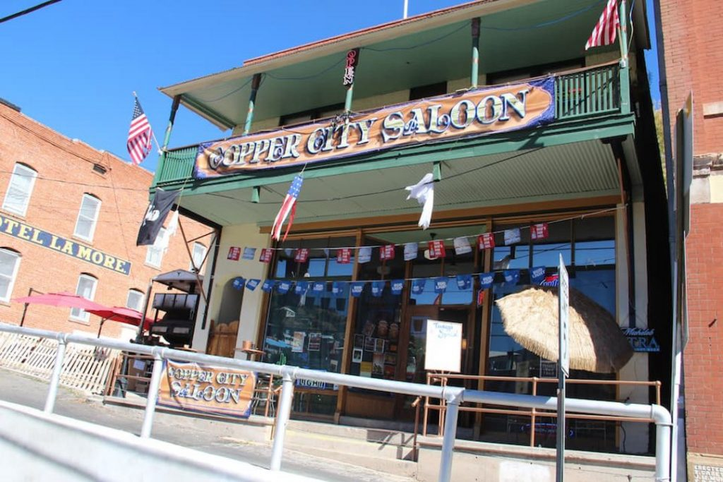 """Two story building with a banner reading """"Copper City Saloon"""" on the second-floor balcony."""