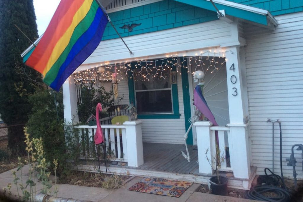 Front of a white house with turquoise trim, decorated with a rainbow flag, pink flamingo, skeleton, and twinkle lights.