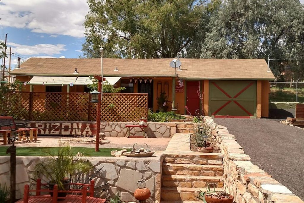 """Golden yellow house with a red X painted on the green garage, behind a stone ledge painted with the word """"Arizona."""""""