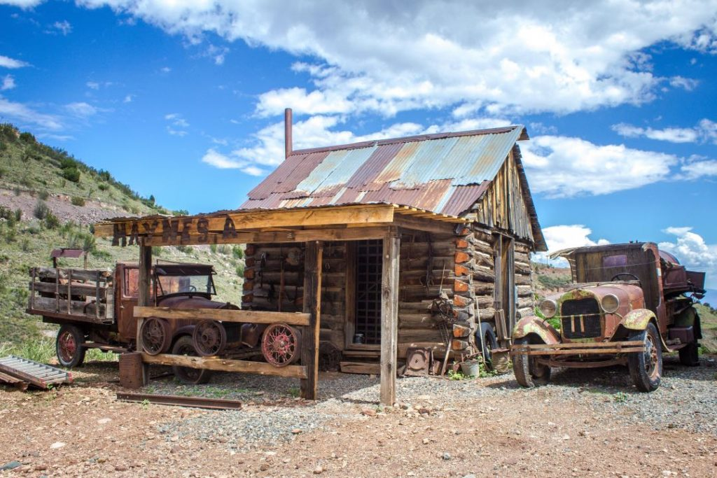 """Rusted trucks next to a log cabin with a tin roof and sign reading """"Haynes, A."""""""