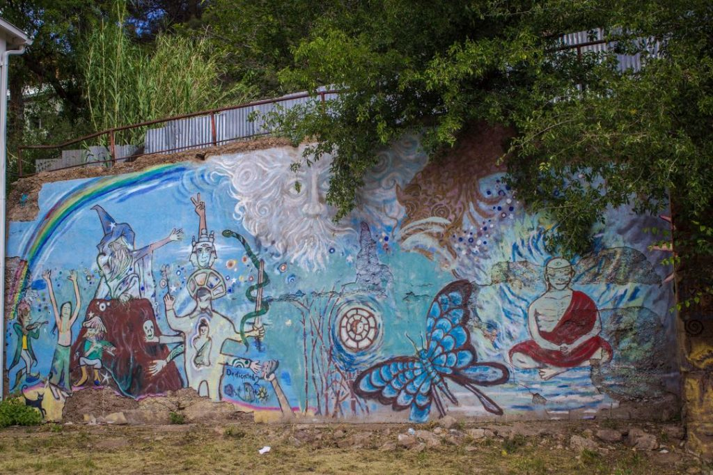 Whimsical mural painted on an outdoor wall.