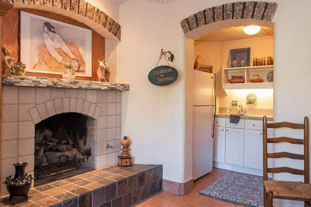 White brick fireplace and wooden place in front of a doorway to the kitchen.