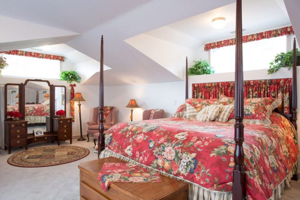 Bedroom with four-post bed covered in a red flowered bedspread, in front of two mauve chairs and a mirrored vanity.