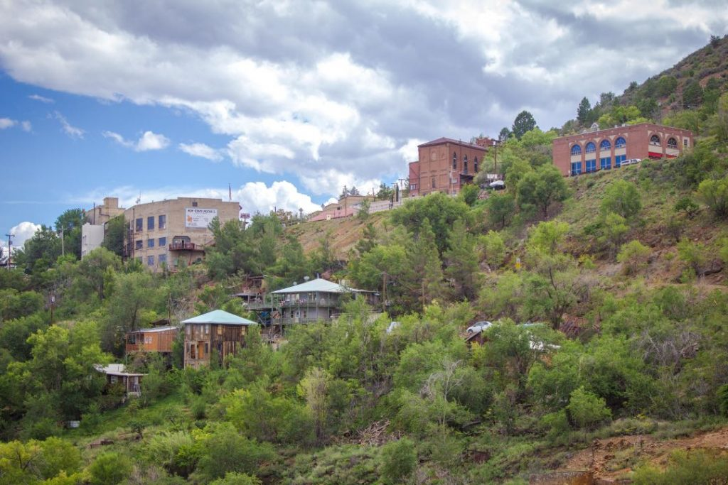 Scattered brick buildings on a hillside of red dirt and trees.