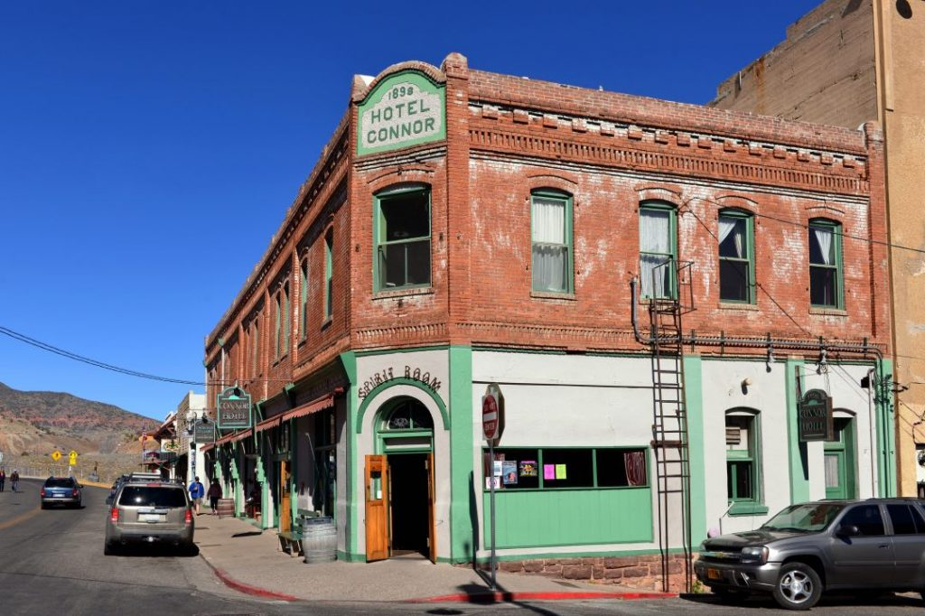 """Two-story brick building with green trim and a sign reading """"1898 Hotel Connor."""""""