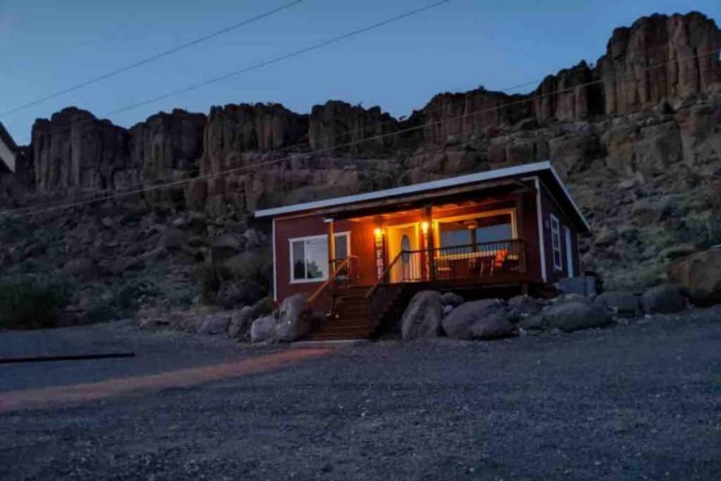 Small bright red cabin with white trim, sitting alone in front of towering sandstone rocks.