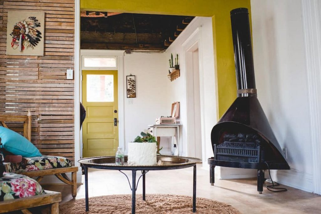 Round table and two chairs in front of a wall of wooden slats and a black wood-fired stove.