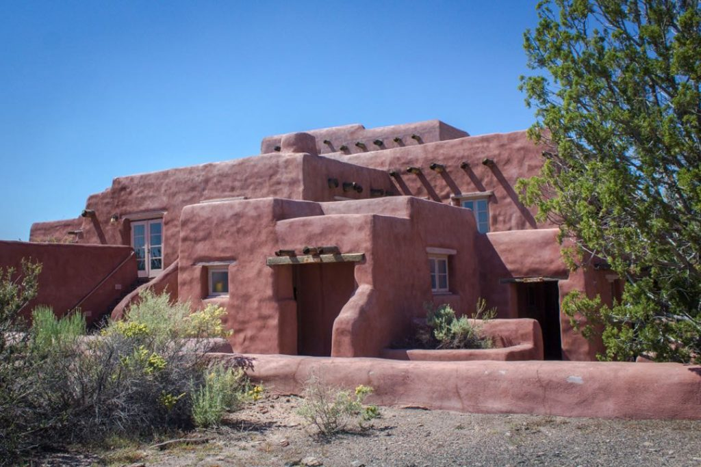 Red adobe-style building with open entrances and glass windows.