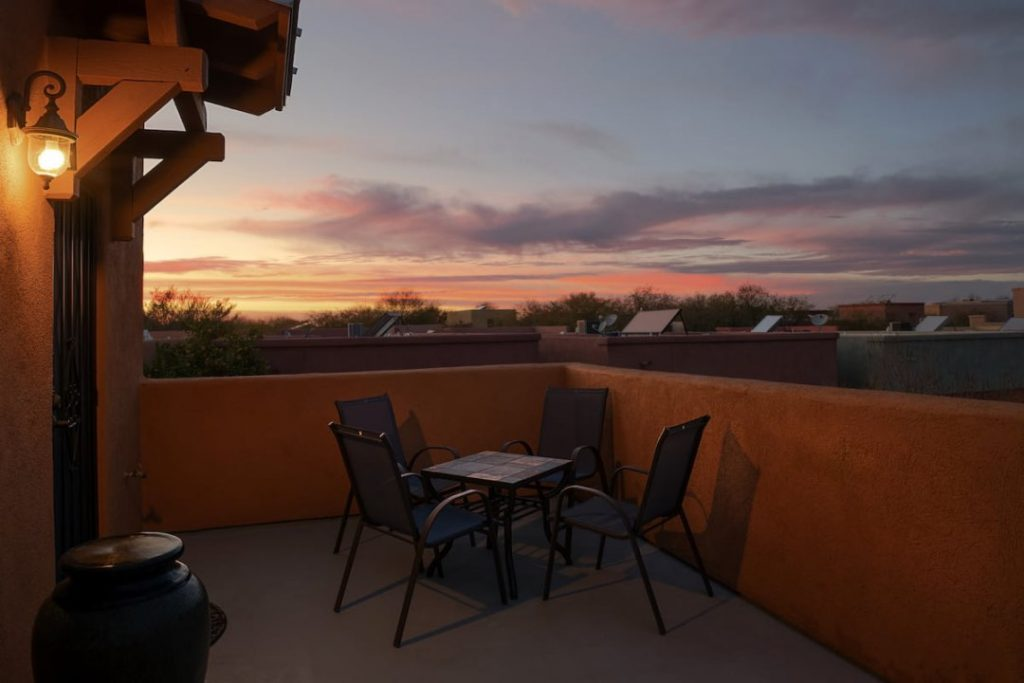 Patio with metal table and chairs and a sunset.