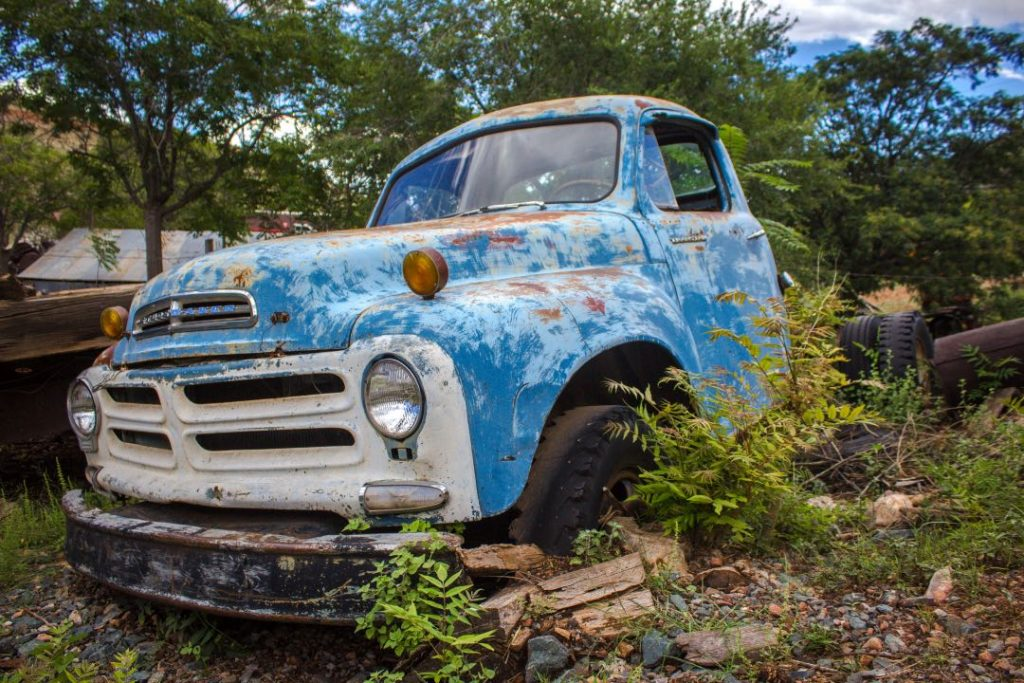Rusted blue vintage pick-up truck sitting among trees.