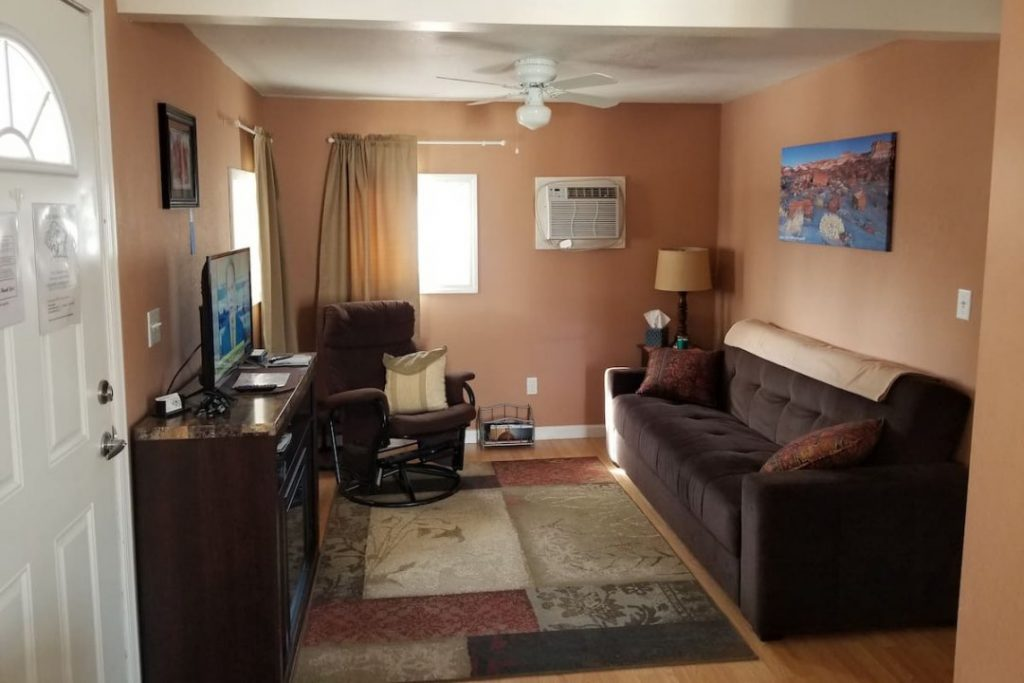Small living room with tan walls and a dark brown couch facing a TV.
